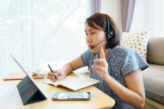 Азиатская женщина с помощью планшета, смотреть урок онлайн-курса общения Premium Фотографии