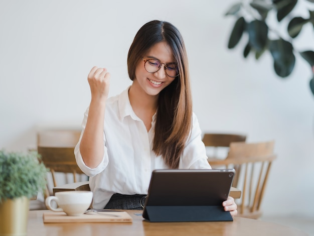Asian woman using tablet with success business deals Premium Photo