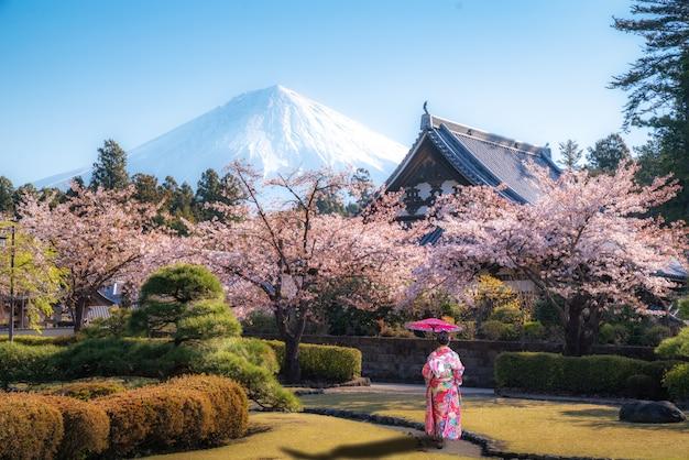 Asian woman walking in temple with mt. fuji in japan Premium Photo