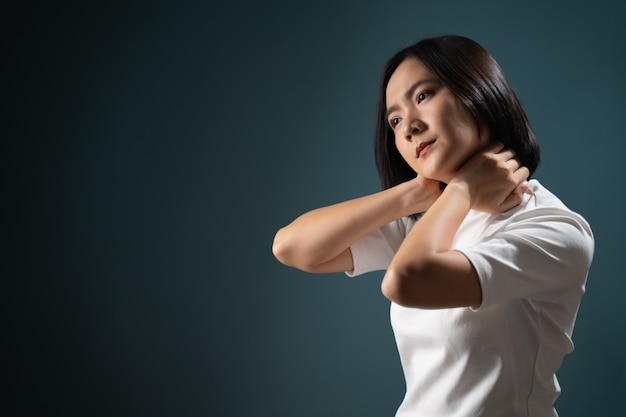 Asian woman was sick with body pain office syndrome and standing isolated over blue Premium Photo