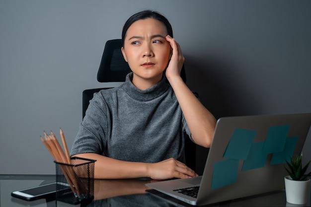 아시아 여자는 두통으로 아팠고, 그녀의 머리를 만지고, 사무실에서 랩톱에서 작업했습니다. 프리미엄 사진