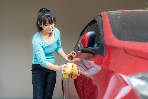 Asian woman washing the car with a sponge | Premium Photo