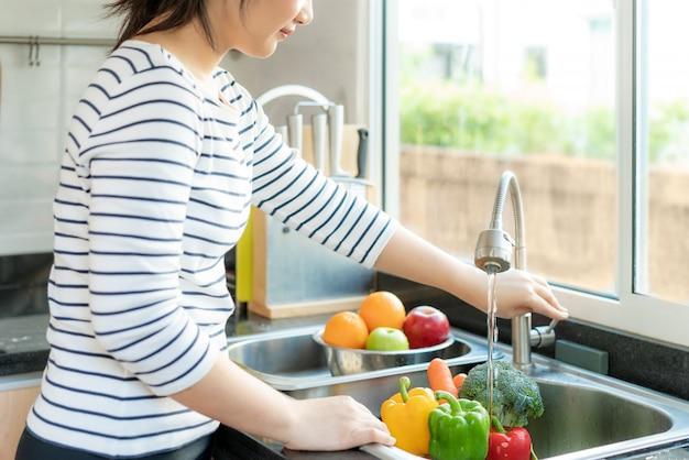 アジアの女性が台所で野菜を洗う Premium写真