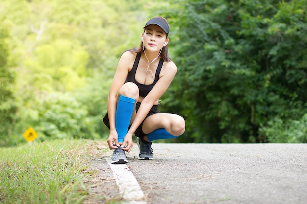 Asian woman wear earphone knelt down to do up shoelaces after running exercise workout Premium Photo