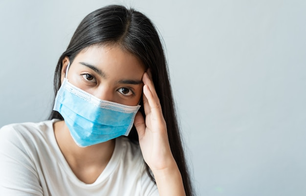 Asian woman wear a face mask are holding their heads because of headaches.she has a fever and migraine because of stress or sleep late, low sleep,insufficient rest in healthy concept with copy space. Premium Photo