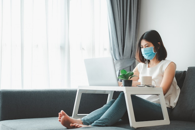 Asian woman wearing face mask working at home Premium Photo