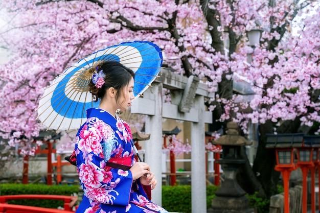 春に日本の伝統的な着物と桜を身に着けているアジアの女性、日本の京都寺院。 無料写真