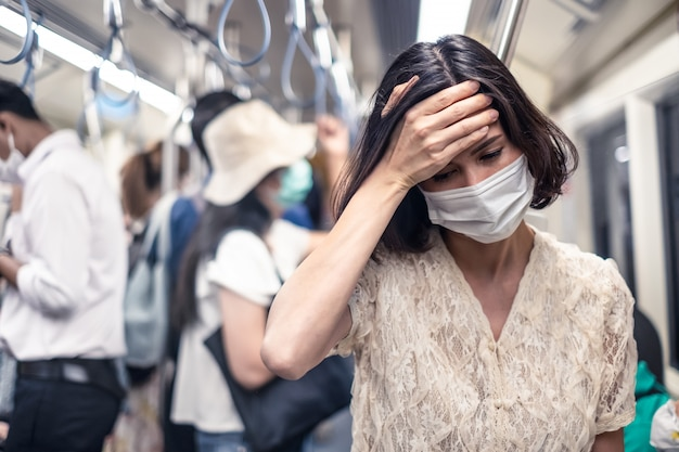 Asian woman wearing mask for prevent dusk pm 2.5 bad air pollution and coronavirus or covid-19 Premium Photo