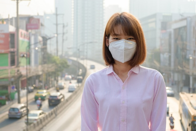 Asian woman wearing the n95 respiratory protection mask against air pollution at road and traffic in bangkok Premium Photo