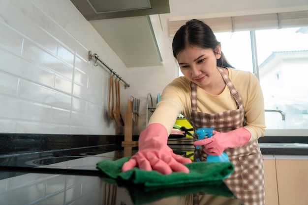 Asian woman wearing rubber protective pink gloves, holding rag and spray. Premium Photo