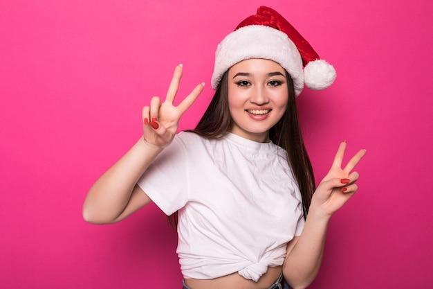 Donna asiatica che indossa il cappello di babbo natale con gesto di pace isolato sulla parete rosa Foto Gratuite
