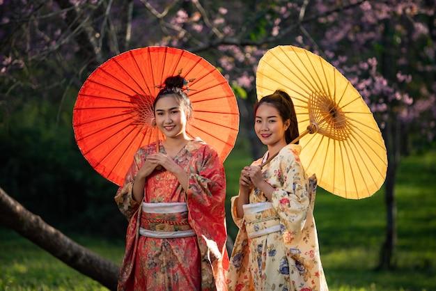 Asian woman wearing traditional japanese kimono, sakura background Premium Photo
