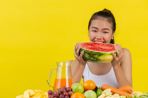 An asian woman wearing a white tank top. both hands hold watermelons and the table is full of various fruits. Free Photo