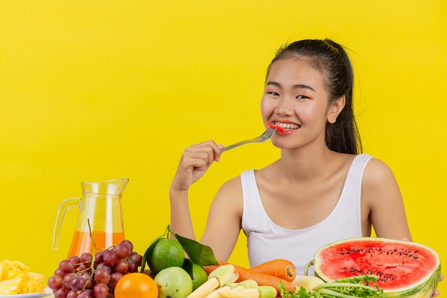 An asian woman wearing a white tank top eating watermelon and the table is full of various fruits. Free Photo
