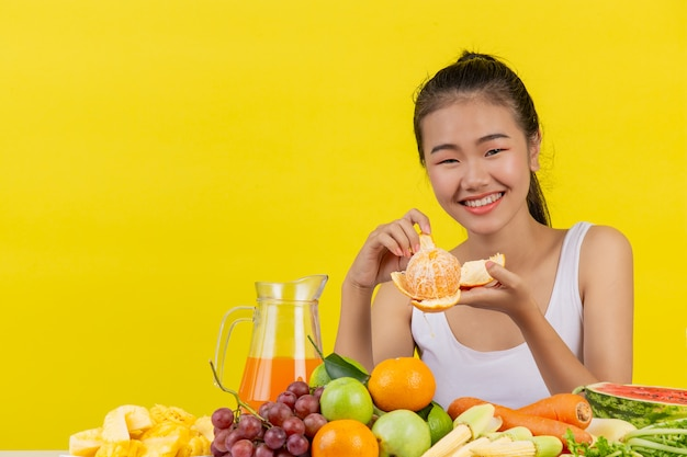 An asian woman wearing a white tank top. i'm peelingorange peel and the table is full of various kinds of fruits. Free Photo