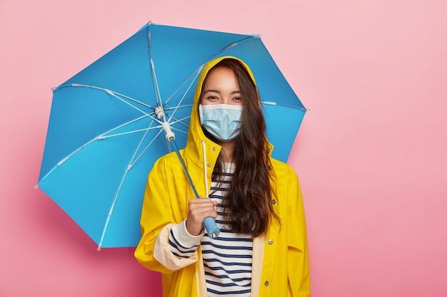 La donna asiatica indossa una maschera protettiva, affronta l'inquinamento atmosferico durante il giorno di pioggia, sta sotto l'ombrello, vestita con un impermeabile giallo Foto Gratuite