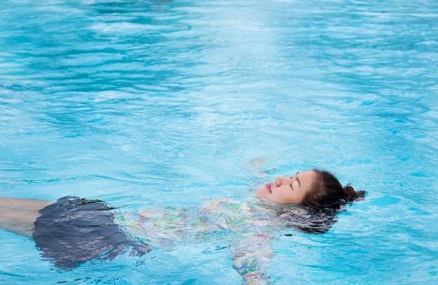Asian woman wears a swimsuit floating in an outdoor pool with clear blue water on a summer holiday. Premium Photo