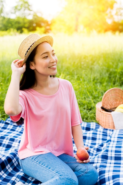 Asian woman with apple sitting on cloth Free Photo