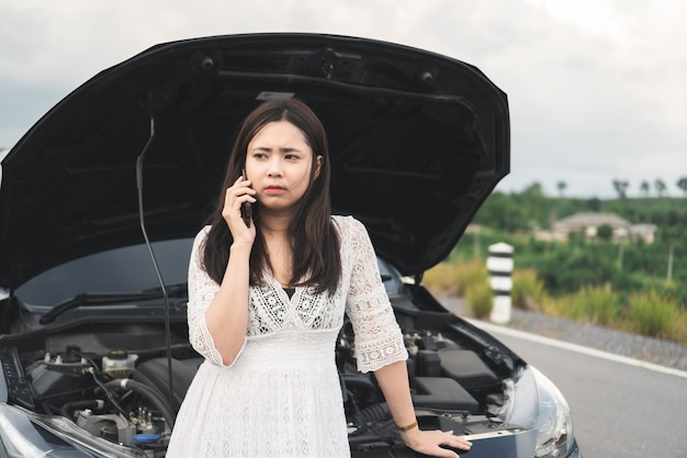 Asian woman with a broken car using mobile phone to call assistance on roadside. Premium Photo
