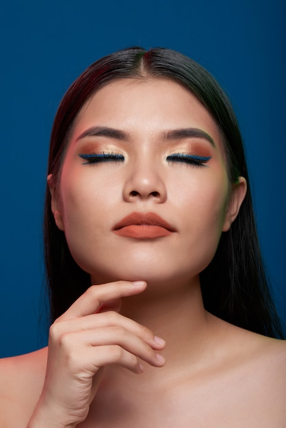 Asian woman with full makeup and bare shoulders posing with closed eyes and finger on chin Free Photo