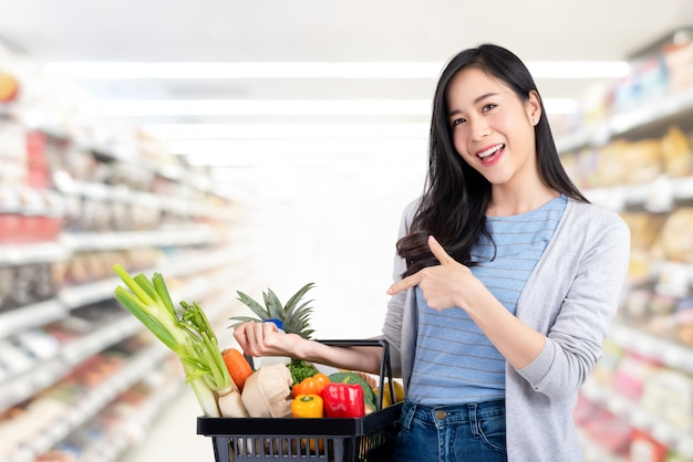 Asian woman with shopping basket full of groceries in supermarket Premium Photo