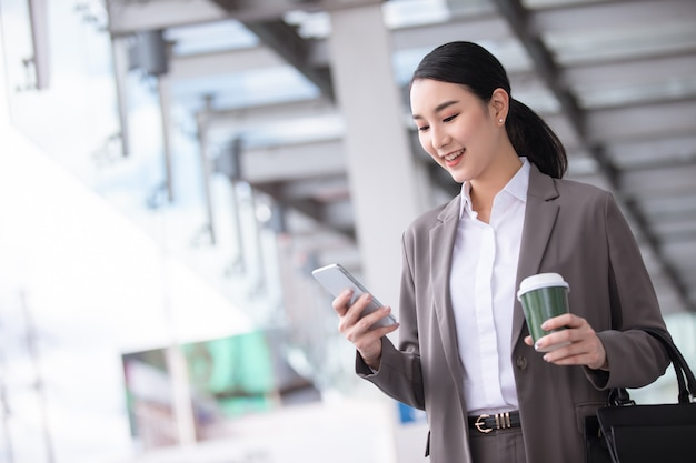 Asian woman with smartphone standing against street blurred building. fashion business photo of beautiful girl in casual suite with phone and cup of coffee Premium Photo