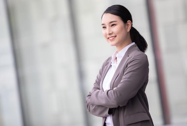 Азиатская женщина с смартфоном, стоящим против затуманенного здания улицы. модное бизнес-фото красивой девушки в повседневном люксе. Premium Фотографии
