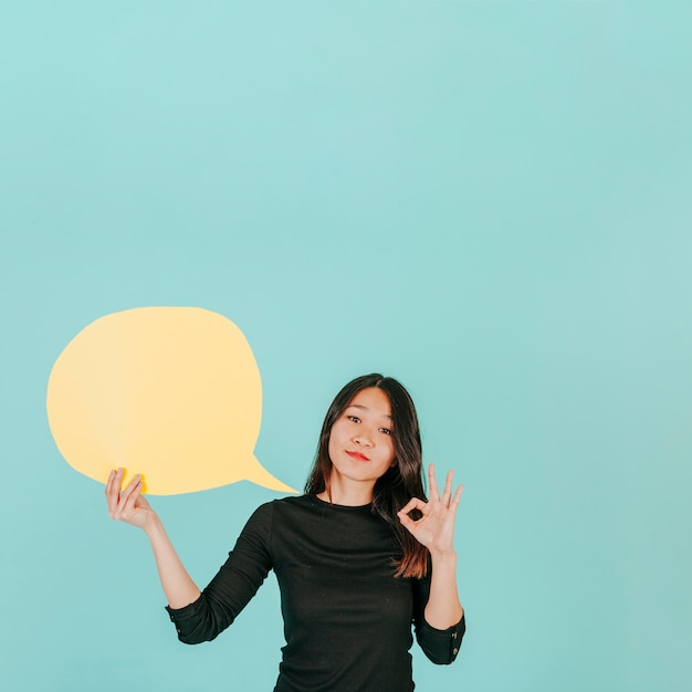Asian woman with speech bubble gesturing ok Free Photo
