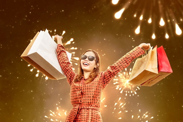 Asian woman with sunglasses carrying a shopping bag with fireworks background Premium Photo
