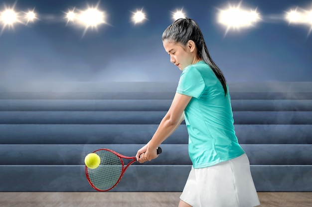 Asian woman with a tennis racket in her hands hit the ball Premium Photo