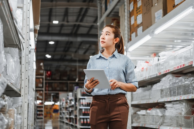 Asian woman worker working with digital tablet checking boxes Premium Photo