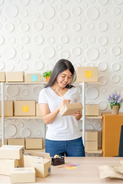Азиатская женщина работая дома с коробками упаковки Premium Фотографии