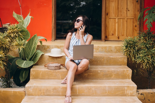 Asian woman working on laptop on a vacation and sitting on the stairs Free Photo