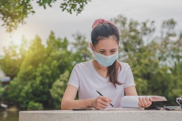 アジアの女性が大学で屋外に座って本を読んで身に着けているフェイスマスク Premium写真