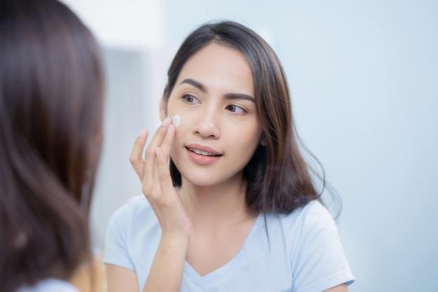 Asian women applying face lotion Premium Photo
