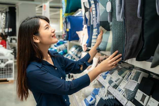 Asian women are choosing to buy new pillows in the mall. shopping for groceries and housewares. Premium Photo