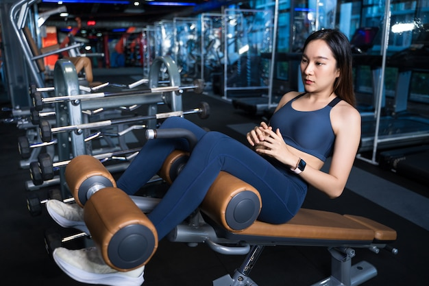 Asian women are determined to train their abdominal muscles with a sit-up pose with a sit-up device. Premium Photo