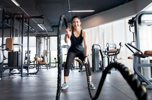 Asian women are exercising in the gym to sift through the leather water, keeping their body healthy. Premium Photo
