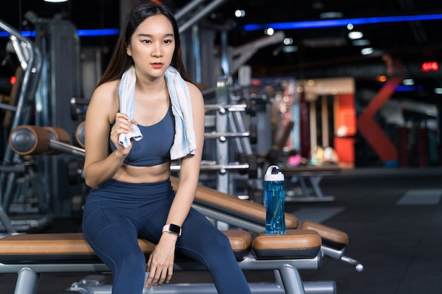Asian women are sitting on the exercise and are holding towels with water bottles placed on their sides Premium Photo