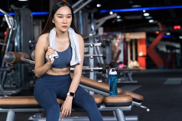 Азиатские женщины сидят на упражнении и держат в руках полотенца с бутылками с водой Premium Фотографии