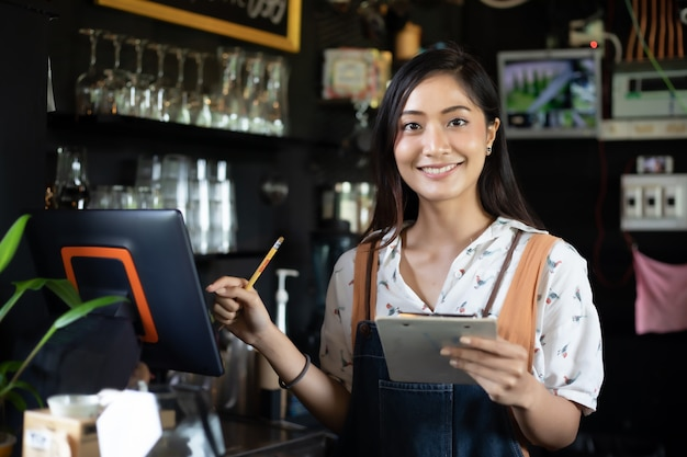 Asian women barista smiling and using coffee machine in coffee shop counter Premium Photo