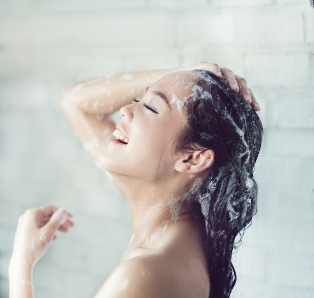 Asian women bathing and she was bathing and washing hair.she is happy Premium Photo