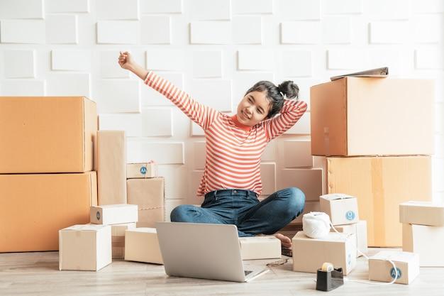 Владелец бизнеса азиатских женщин, работающих дома с упаковочной коробкой на рабочем месте Premium Фотографии