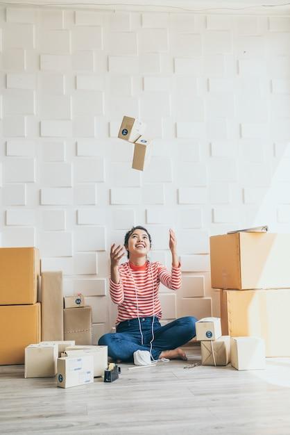 Владелец бизнеса азиатских женщин, работающих на дому с упаковочной коробки на рабочем месте Premium Фотографии