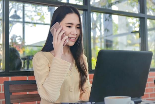 アジアの女性が携帯電話事業契約のオンライン技術を自宅から呼び出す Premium写真