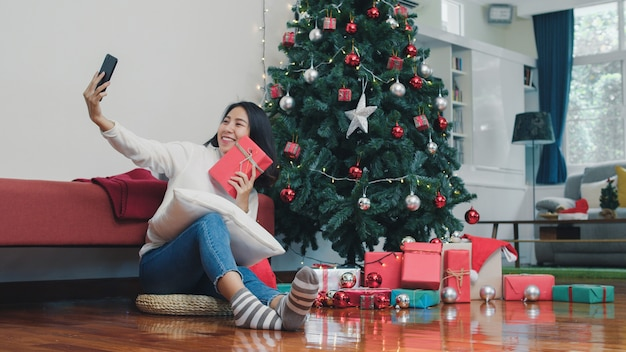 Asian women celebrate christmas festival. female teen relax happy holding gift and using smartphone selfie with christmas tree enjoy xmas winter holidays in living room at home. Free Photo