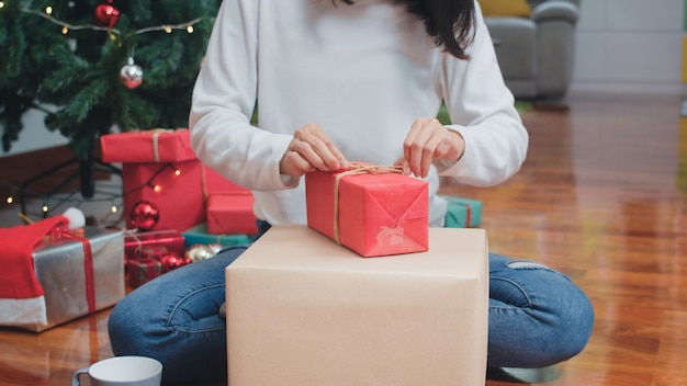 Asian women celebrate christmas festival. female teen wear sweater and christmas hat relax happy wrapping gifts near christmas tree enjoy xmas winter holidays together in living room at home. Free Photo