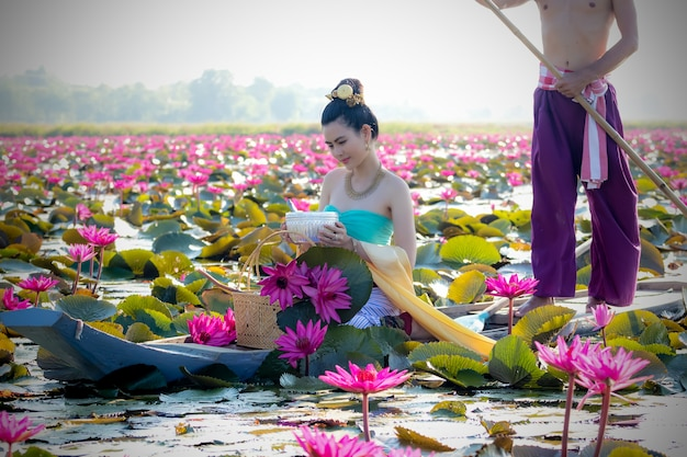 Asian women collecting red lotus to bring to worship with the monks on a religious day. Premium Photo
