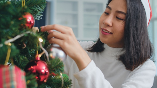 Asian women decorate christmas tree at christmas festival. female teen happy smiling celebrate xmas winter holidays in living room at home. close up shot. Free Photo