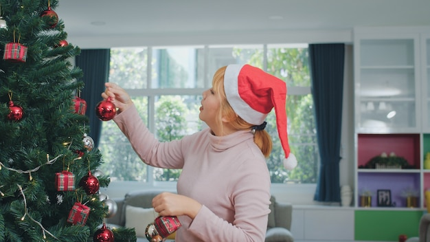 Asian women decorate christmas tree at christmas festival. female teen happy smiling celebrate xmas winter holidays in living room at home. Free Photo